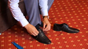 Man is tying his black shoes. Close-up stock footage