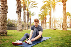 Man tying his shoelaces. A photo of young, sporty man sitting on the gym mat at the park and tying his shoelaces Royalty Free Stock Images