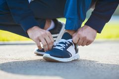 Tuning sport shoes before training. A man tying his shoelaces before starting workout Royalty Free Stock Photos