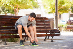 Man tying his shoes before going for a run. Portrait of a good looking young man tying his shoes and getting ready to go jogging in a park Stock Image