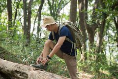 Man hiker tying his shoes. Man tying his shoes while hiking in the forest Royalty Free Stock Photography