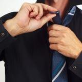 Man tying his tie over black shirt closeup Stock Photo