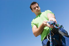 Man Tying a Knot. Attractive, fit young man tying a knot in a climbing rope. Set against a clear blue sky Stock Photo