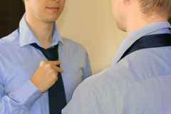 Man tying necktie standing in front of mirror Royalty Free Stock Photography