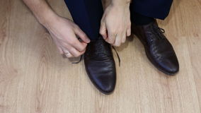 Man tying patent leather shoes formal and festive dressing. stock video