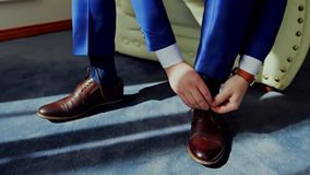 Man tying patent leather shoes. stock footage