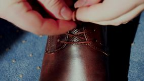 Man tying patent leather shoes. stock video