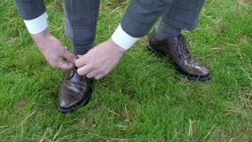 Man tying patent leather shoes on the grass. Man tying patent leather shoes formal and festive dressing. Slowmotion. Close up stock video footage