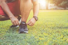 Man tying rope on his sports shoe. Preparing for run in the park stock photos