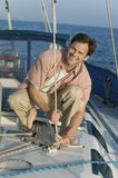 Man Tying Rope On The Yacht Royalty Free Stock Photography