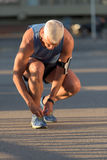 Man tying running shoes laces. Before jogging workout Stock Image
