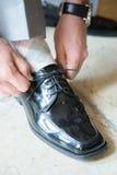 Man tying shiny black shoes stock photos