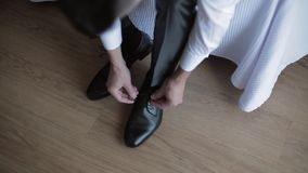 Man tying shoe laces. Groom sitting on bed and tying shoe laces for wedding ceremony stock video footage
