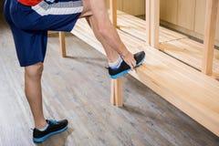 Man tying shoelace in locker room Stock Photo