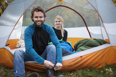 Man Tying Shoelace While Woman Relaxing In Tent Royalty Free Stock Photo