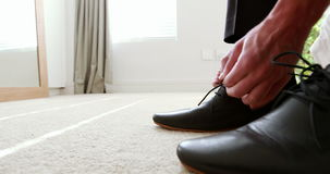 Man tying a shoelaces in bedroom stock video footage