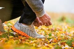 Man tying shoelaces. Closeup of man tying shoelaces on autumn grass in park Royalty Free Stock Image