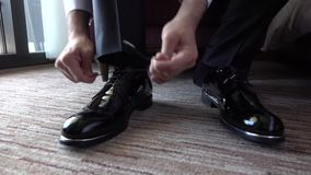 Man Tying Shoelaces on Expensive Black Shoes