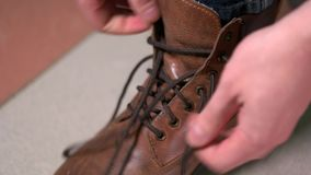 Man tying shoelaces on expensive brown shoes. 4K stock video footage