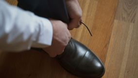 Man tying shoelaces. Indoors closeup shot stock video