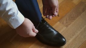 Man tying shoelaces. Indoors closeup shot stock footage