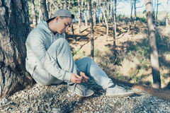 Man tying shoelaces outdoor. Sporty young man tying shoelaces outdoor near a tree in the forest Stock Photo