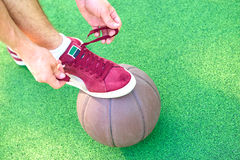 Man tying shoelaces relying on basketball ball Stock Photos