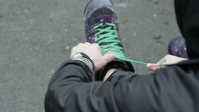 Man tying shoelaces on special snowboard boots. Man tying shoelaces  on special snowboard boots. Close-up stock footage
