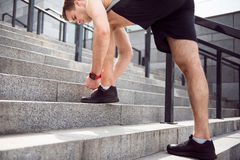 Man tying shoelaces on stairs Stock Image