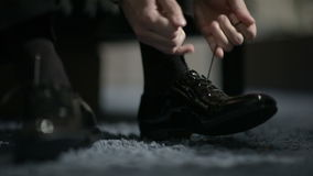Man tying shoes. Man tying patent leather shoes. Formal and festive dressing stock video