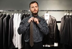 Man tying a tie. Handsome man with beard tying a tie in a clothing store royalty free stock photography
