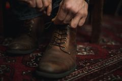 Man tying up his boots. Closeup of male hands lacing up and tying his old brown leather boots Royalty Free Stock Photos