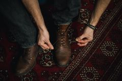 Man tying up his boots. Closeup of male hands lacing up and tying his old brown leather boots Royalty Free Stock Photography