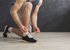 Man tying up lace on sport shoes closeup. Unrecognizable guy preparing for training, wearing sneakers, copy space Royalty Free Stock Images