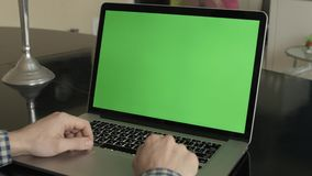 A Man Types on a Laptop on His Desk. Green screen for your custom screen content stock video footage