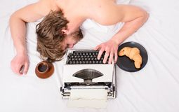 Man with typewriter coffee lay bed. Man sleepy lay bedclothes while work. Writer used old fashioned typewriter. Workaholic fall asleep. Author tousled hair royalty free stock images