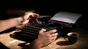 Man typing a typewriter at night creates a new novel. Man on a typewriter creates a new novel at night, on the table lie old books and a cup of tea stock footage