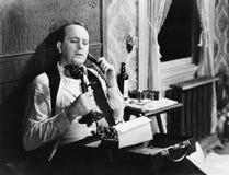 Man with typewriter talking on phone Stock Images