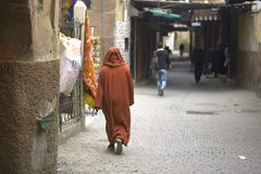 The man in the typical Arabian brown dress walks through the alleys of the old city. Journey through colors, traditions and religions of the Muslim world Stock Photos