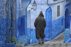 A man in typical moroccan clothing, blue Medina of Chefchaouen. A man in typical moroccan clothing, walking down a street in the blue Medina of Chefchaouen Royalty Free Stock Images