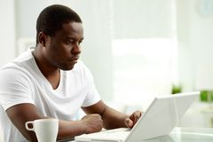 Man typing. Image of young African man typing on laptop at home Stock Images