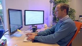 Man typing behind a computer with two screens stock footage
