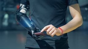 Man typing with bionic prosthesis. Cyborg concept. Young man works with a phone, wearing an artificial arm
