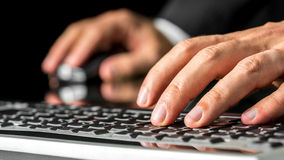 Man typing on a computer keyboard. Close up low angle view of the left hand of a man typing on a computer keyboard inputting data with his other hand on the Stock Photo