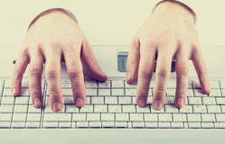Man typing on a computer keyboard. Toned instagram effect image of a man typing on a computer keyboard inputting data or information stock images