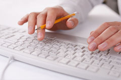 Man typing on a computer keyboard at work. Holding a pencil in the fingers of one hand as he enters data, close up view stock images