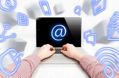 Man typing e-mail in flow of flying IT icons Royalty Free Stock Photos