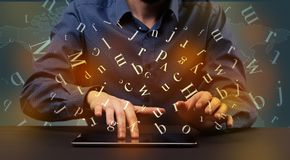 Man typing in formal clothing and letters around Stock Photo