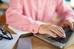 Man typing. Hands of senior man over laptop keypad and fingers pressing buttons while typing stock image