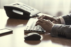 Man typing on keyboard. Businessmen in suits write a letter on personal computer in the office royalty free stock photo